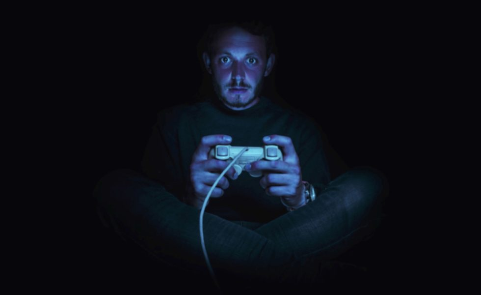 A young man holding a video game controller, lit only by the blue hue of a video game screen