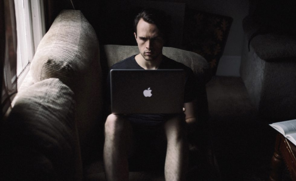 A young man sitting on a couch intensely engaged with his laptop