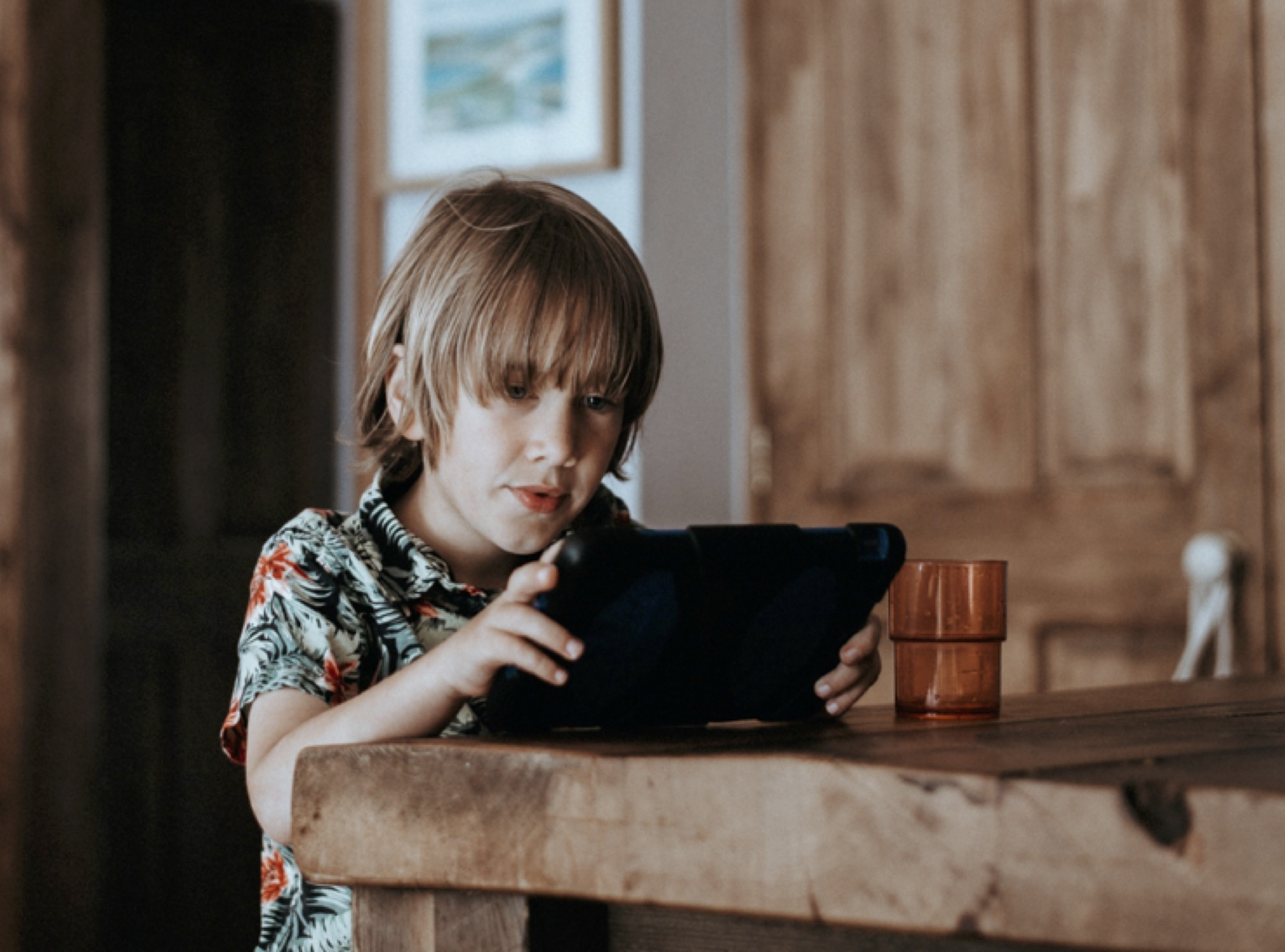 A boy sitting at a table using an iPad